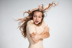 The woman with hair blowing in the wind on gray - stock photo