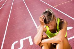 Sporty woman sitting down and feeling disappointed  against race track Stock Photos