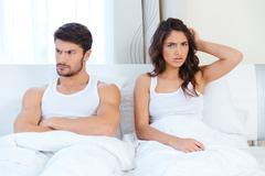 Unhappy separate couple lying in a bed - stock photo