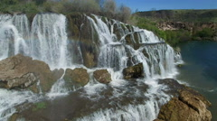 Flying view of waterfall flowing over edge into river Stock Footage