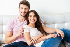 Smilling young couple on the sofa over white background - stock photo