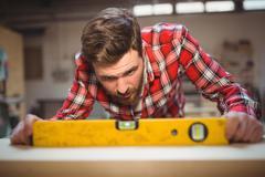 Carpenter using spirit level to measure Stock Photos