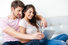 Smiling couple using pc tablet over white background - stock photo