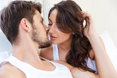 Close-up portrait of a pretty kissing couple in bed Stock Photos