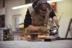 Worker using an angle grinder Stock Photos
