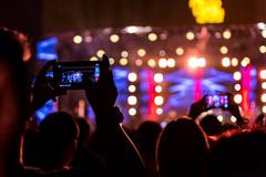 People holding their smart phones shooting video or photo. - stock photo