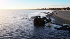 Tractor removes algae on coast of Baltic Sea - stock footage