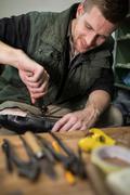 Cobbler repair shoes sole in workshop Stock Photos