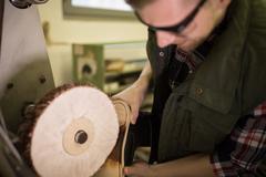 Cobbler using a machine on a shoe sole Stock Photos