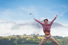 Man jumping with golf club against country scene - stock photo