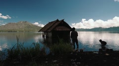 Fisherman and little boy cathing fish in Batur Lake near a small hut Stock Footage