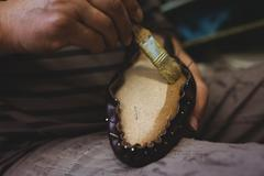 Cobbler applying glue on shoes Stock Photos
