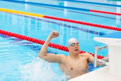 Young male swimmer celebrating victory in the swimming pool Kuvituskuvat