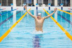 Dynamic and fit swimmer in cap breathing performing jumping out the water Stock Photos
