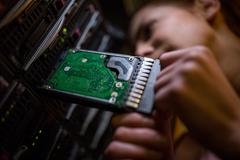 Technician inserting a hard disk drive into a blade server Stock Photos