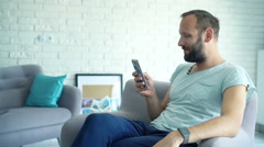 Young man sitting on armchair with smartphone in living room at home Stock Footage