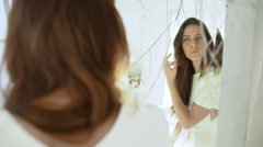 Young beautiful girl looking in mirror in white decor. Slow motion Stock Footage