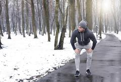 Young man taking a break from exercise, in snowy forest Stock Photos