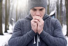 Young man breathing on hands, in snowy forest Stock Photos