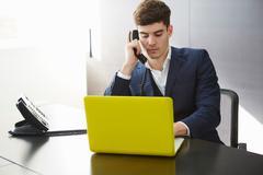 Man sitting at desk using laptop making telephone call Stock Photos