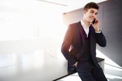 Man sitting on desk making telephone call smiling Kuvituskuvat