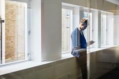 View through glass of man leaning against windowsill looking down at smartphone Stock Photos