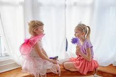 Two young girls, in fancy dress, sitting face to face Stock Photos