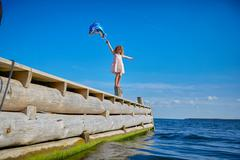 Young girl standing on wooden post on pier, holding helium balloon Stock Photos