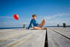 Young boy sitting on wooden pier, holding red helium balloon Stock Photos