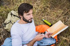 Man in sleeping bag planning with map and smartphone in forest, Deer Park, Cape Stock Photos