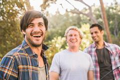 Three men laughing whilst putting up tent in forest, Deer Park, Cape Town, South Stock Photos