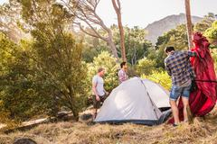 Three men putting up dome tent in forest, Deer Park, Cape Town, South Africa Stock Photos