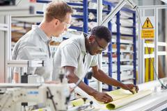 Manager mentoring worker on production line in roller blind factory Stock Photos