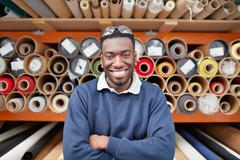 Portrait of male factory worker in front of textile rolls in roller blind Stock Photos