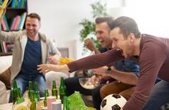 Group of men watching sporting event on television holding football celebrating Stock Photos