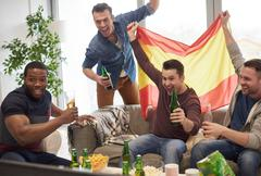 Group of men watching sporting event on television holding Spanish flag Stock Photos