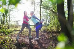 Side view of women in forest face to face holding ankle stretching leg Stock Photos