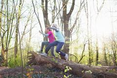 Side view of women in forest jumping over fallen tree Stock Photos
