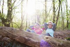 Women in forest hands behind head doing sit up against fallen tree Stock Photos