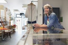 Shop assistant leaning against glass counter looking away smiling Stock Photos