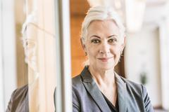 Businesswoman leaning against glass door looking at camera smiling Stock Photos