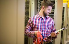 Technician holding patch cable and reading notes Stock Photos