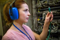 Technician in head phones looking at patch cable Stock Photos