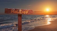 Holiday Signboard on Beach Stock Photos