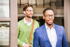 Two businessmen leaving office building Stock Photos