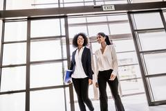 Two young businesswomen arriving at office entrance Stock Photos