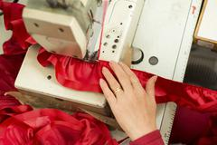 Hand on Sewing Machine Stitching Red Ribbon and Ruffled Cloth - stock photo