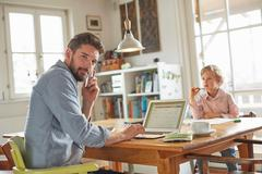 Father on phone while working in home office with son Stock Photos