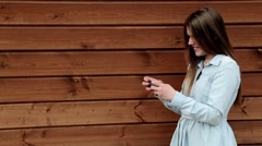 Teenage girl typing on her smartphone wooden background copy space - stock footage