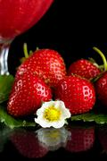 Cropped view of strawberry with goblet,leaves,flower on black background - stock photo